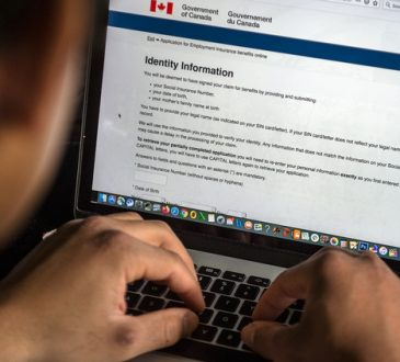 man navigating government of canada website on laptop