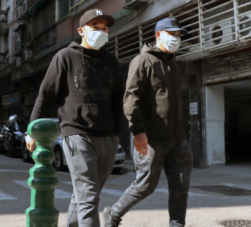 two men wearing masks walking down street