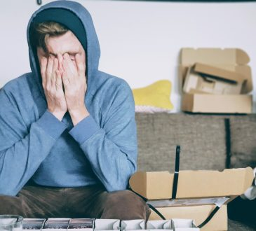 stressed male student wearing hoodie with head in hands