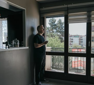 man standing in empty apartment