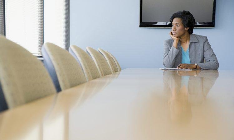 woman sitting alone in boardroom