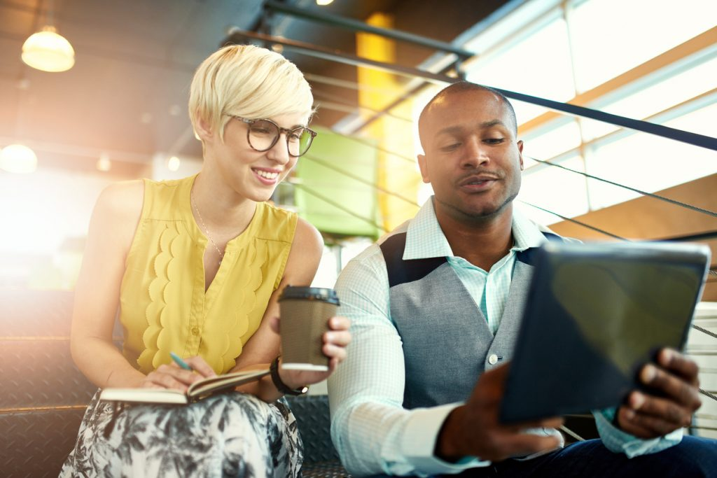 man and woman looking at tablet together in office