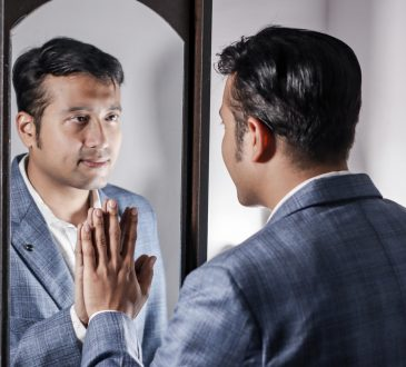 man in suit looking in mirror