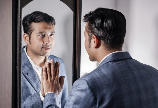 man in suit looking in mirror