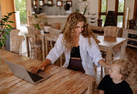 woman working at home with young child