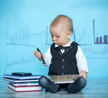 baby boy wearing suit, holding pen and tablet beside stack of books