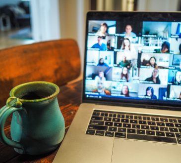 mug and laptop open with video conferencing call