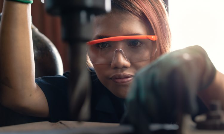 young woman using drill press