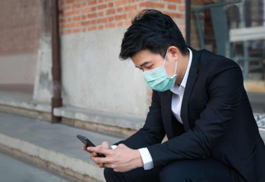 male student in suit looking at phone wearing mask
