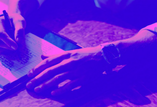photo of person writing on paper with purple filter