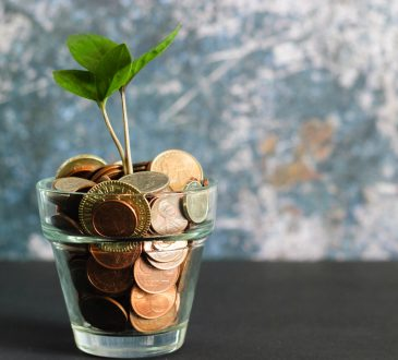 money in glass with plant sprouting out