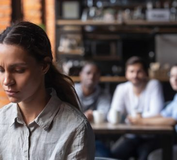 sad woman sitting apart from co-workers