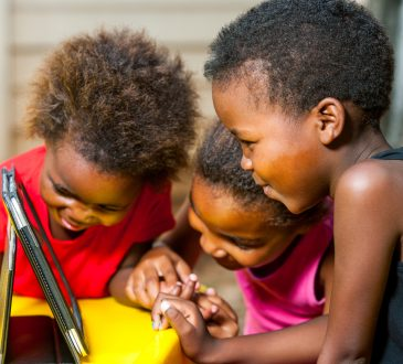 three young Black students using tablet