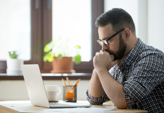 Young bearded man working and reading data on laptop in home office.