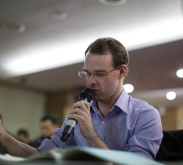 Man Sitting and Speaking into Microphone