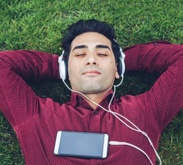 Young man relaxing in the park and listening music
