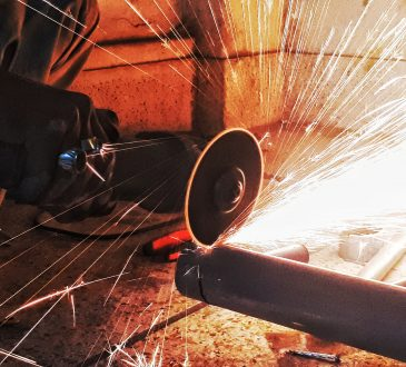 sparks flying as person saws pipe