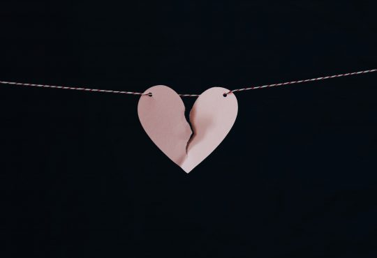paper cutout broken heart hanging on string