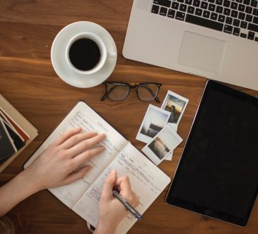 person writing in notebook on cluttered desk