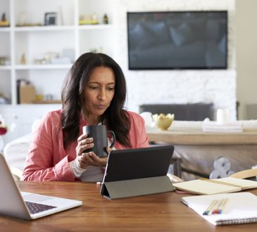woman sitting at a table reading using a tablet computer