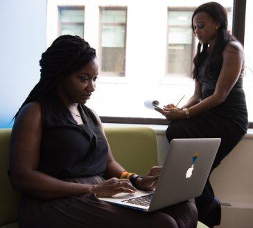 two women working on laptops