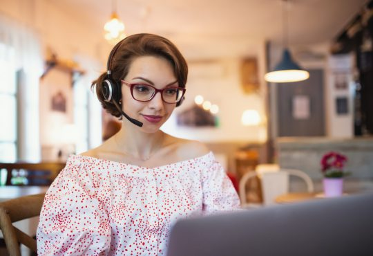 Portrait of young woman with headset and laptop indoors in cafe, working.