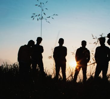 group of young people hanging out in field