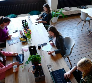 women working around long desk in office