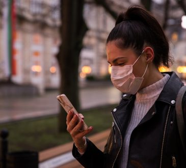 Side view of young woman with face protective mask in a city at dusk