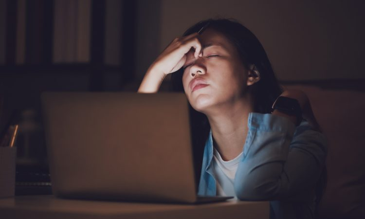 woman sitting at computer looking stressed