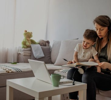 woman trying to work on couch with son in lap