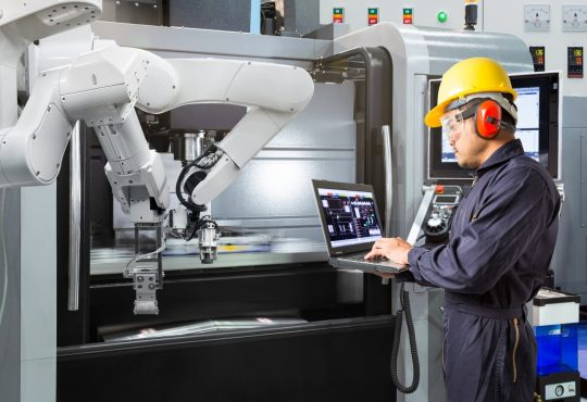 man working with robot machine in factory