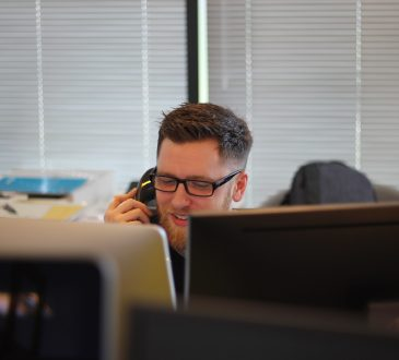 man using phone in office