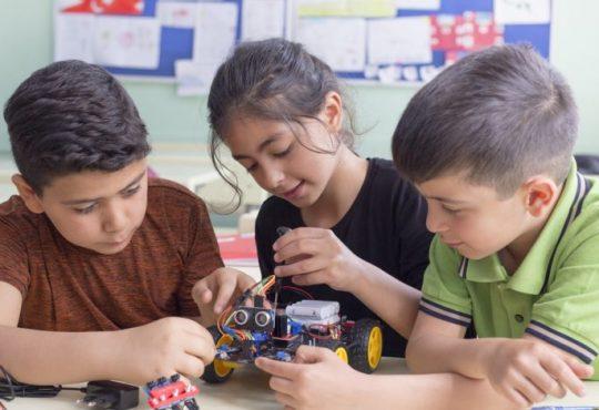 three kids in elementary school classroom