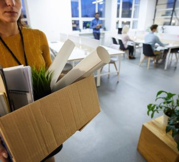 person carrying box out of office after being fired