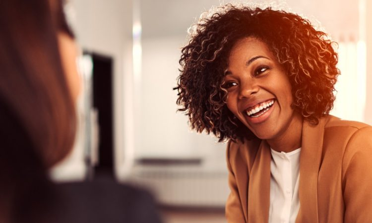 young black businesswoman talking to coworker