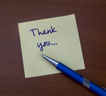 A thank you card with a fountain pen on a wooden desk