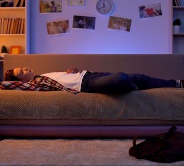 teen lying on basement couch