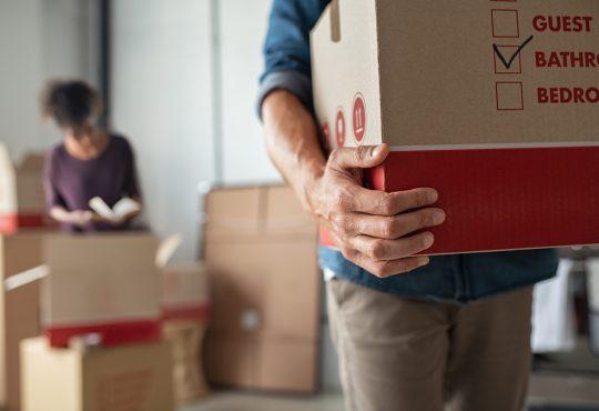 Closeup of man hand holding cardboard box at new home.