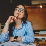 woman sitting at desk thinking