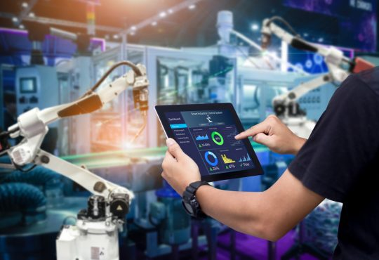 person using tablet alongside robot worker