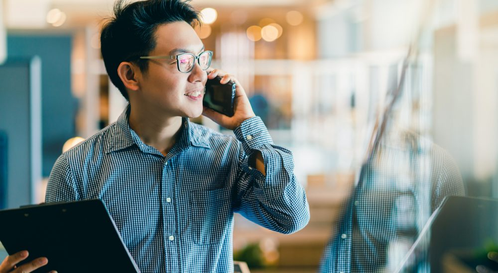 man talking on phone while walking in office