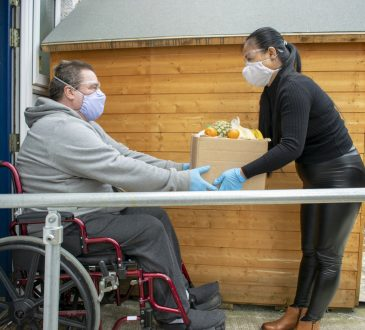 Helper Delivering Food to a Disabled Man in Quarantine
