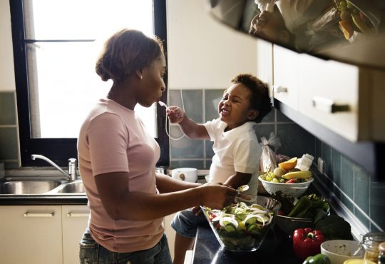 mom and child cooking together in kitchen