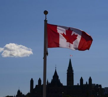 canadian flag in front of parliament hill
