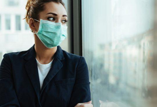 woman wearing mask looking out window