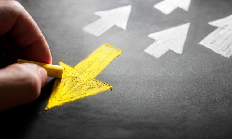 person drawing yellow arrow on chalk board pointing away from white arrows