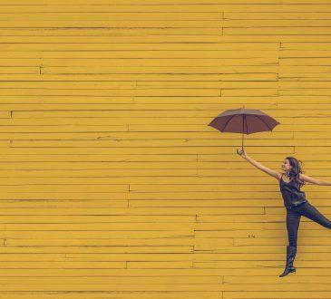 "woman ""flying"" holding umbrella on backdrop of yellow brick wall"
