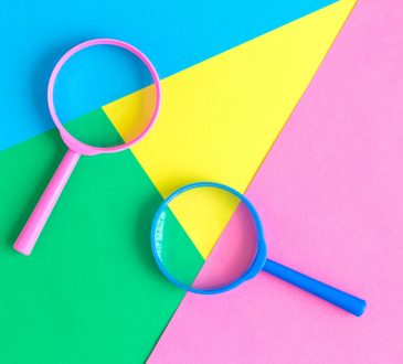 magnifiying glasses on colourful geometric background