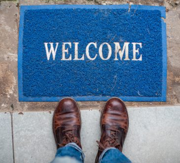 Person with boots standing in front of welcome mat